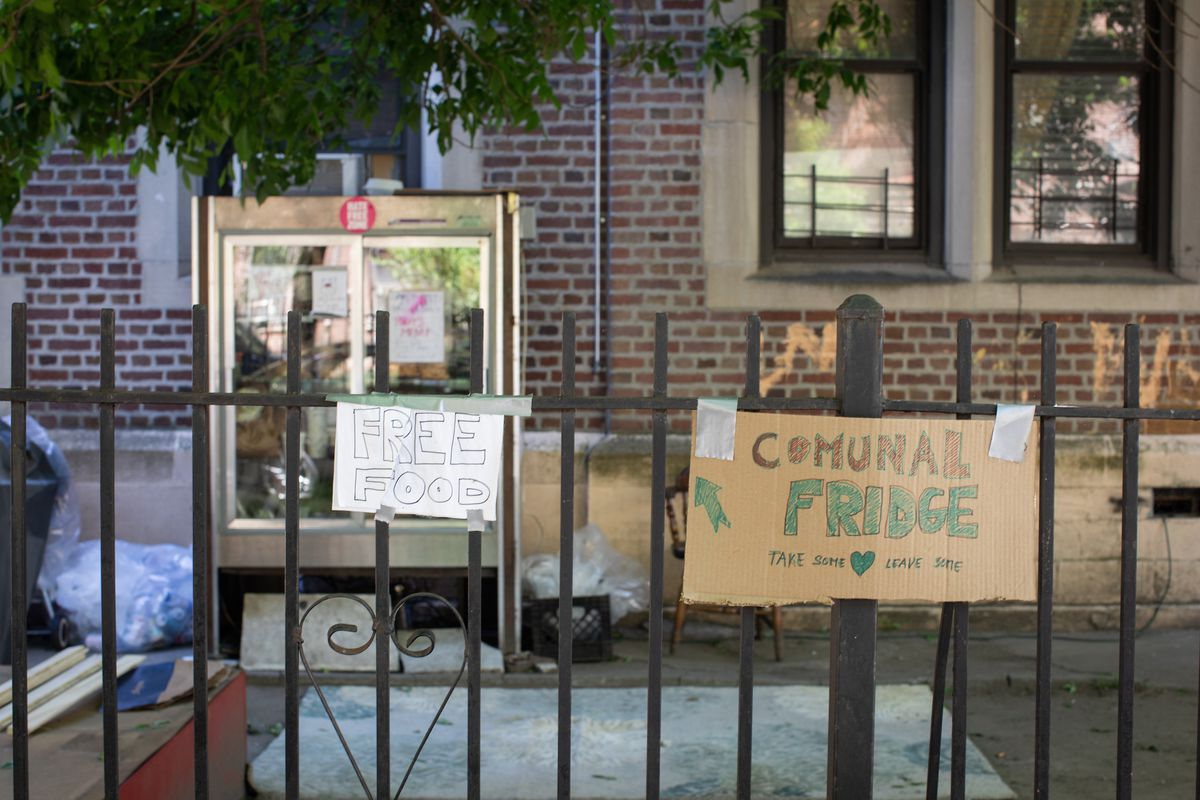 Two handmade signs advertising a community fridge taped up to a gate, with the fridge in the background.