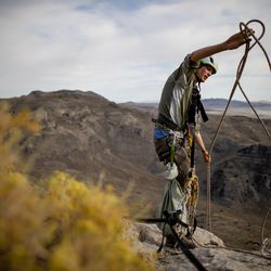 Hawkwatch International research associate Dustin Maloney pulls up his rigging after finding two golden eagle nestlings were dead in their nest in Tooele County on Friday, June 18, 2021.
