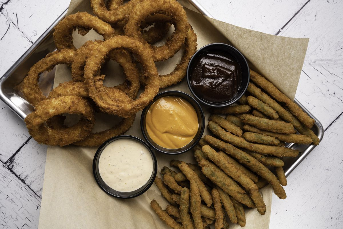 A silver cookie sheet with onion rings and fried green beans