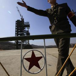 A North Korean soldier stands in front of the country's Unha-3 rocket, slated for liftoff between April 12-16, at Sohae Satellite Station in Tongchang-ri, North Korea on Sunday April 8, 2012. North Korean space officials have moved a long-range rocket into position for this week's controversial satellite launch, vowing Sunday to push ahead with their plans in defiance of international warnings against violating a ban on missile activity. (AP Photo/Ng Han Guan)