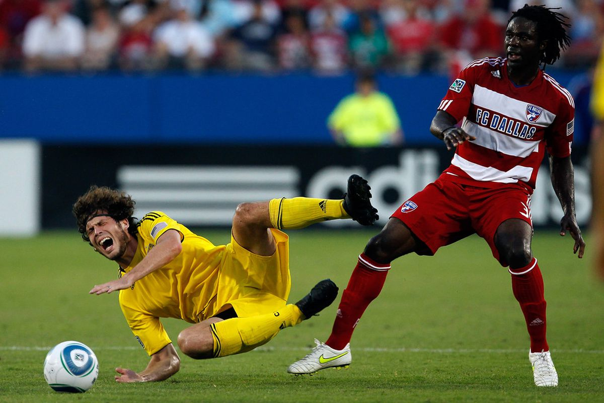 FRISCO, TX - JULY 02:  Tom Heinemann #32 of the Columbus Crew (L) is tripped up by Ugo Ihemelu #3 of the FC Dallas at Pizza Hut Park on July 2, 2011 in Frisco, Texas.  (Photo by Tom Pennington/Getty Images)