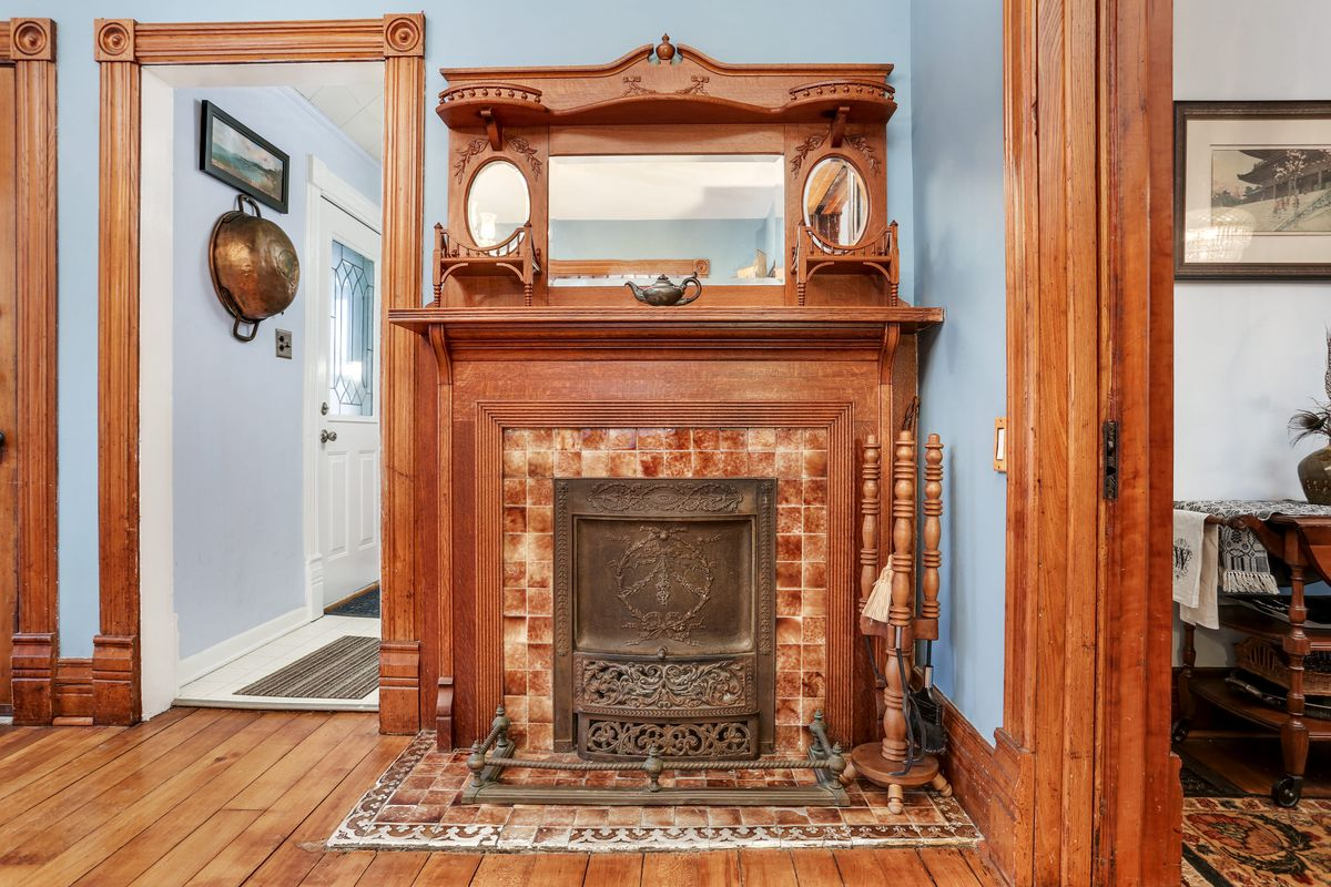 A view of the fireplace with deep brown tiles and fireplace. Two tiny oval mirrors sit on the mantel and there's an iron grate.