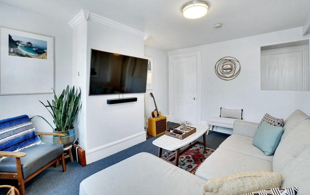 A snug living room with a couch facing a mounted TV, and there's a guitar and amp next to the TV.