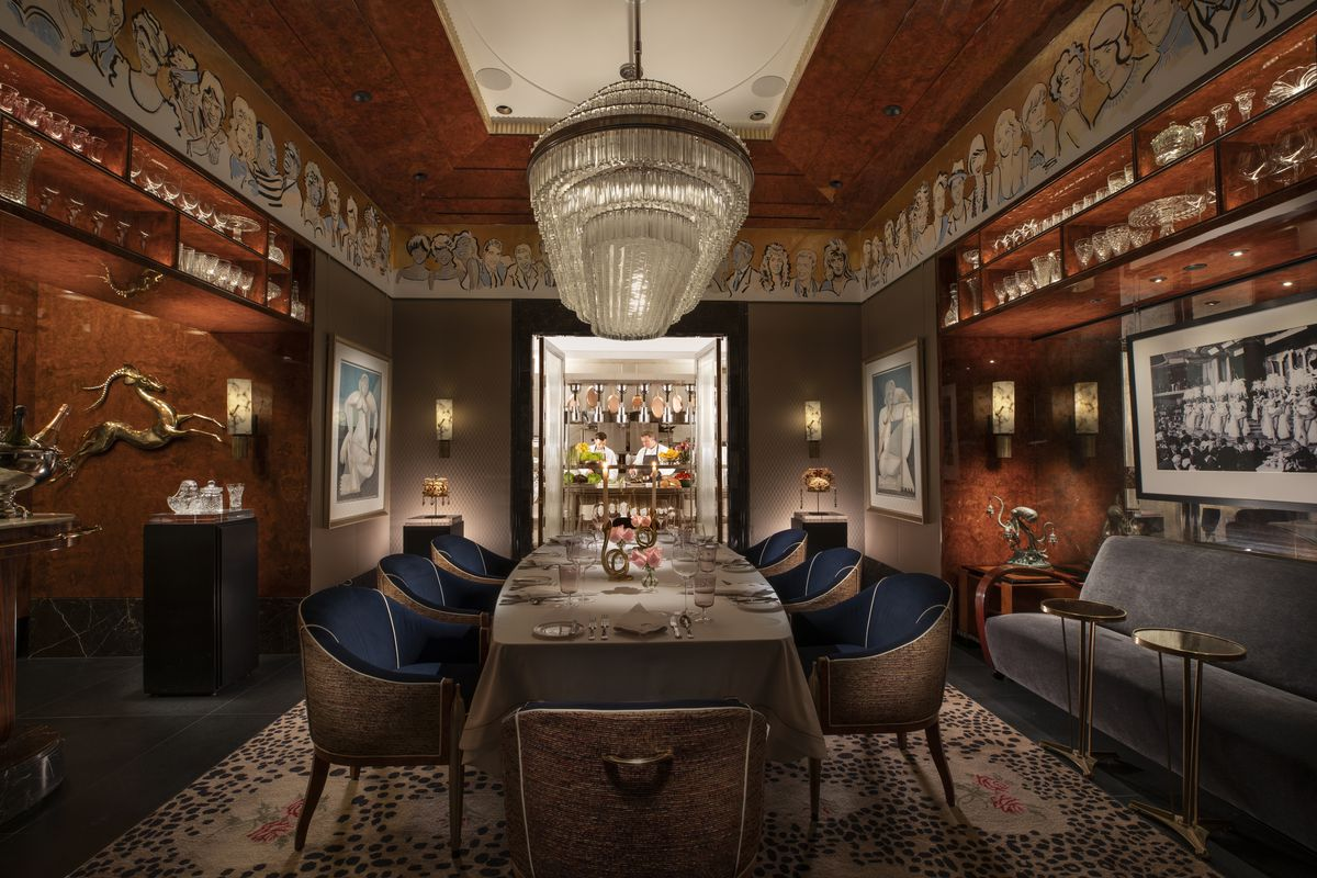 A private dining room with blue chairs and a view of the kitchen