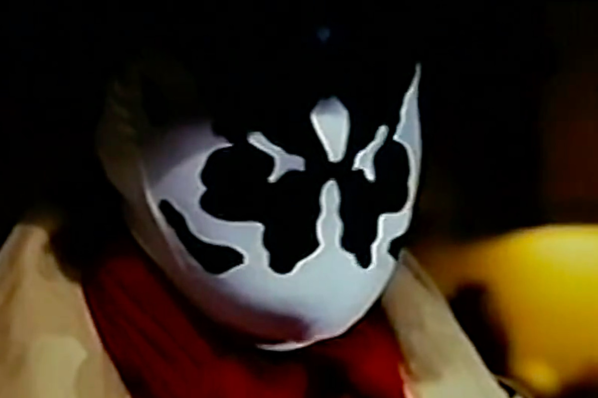 rorschach sits in close up in a kitchen wearing his inkblot mask