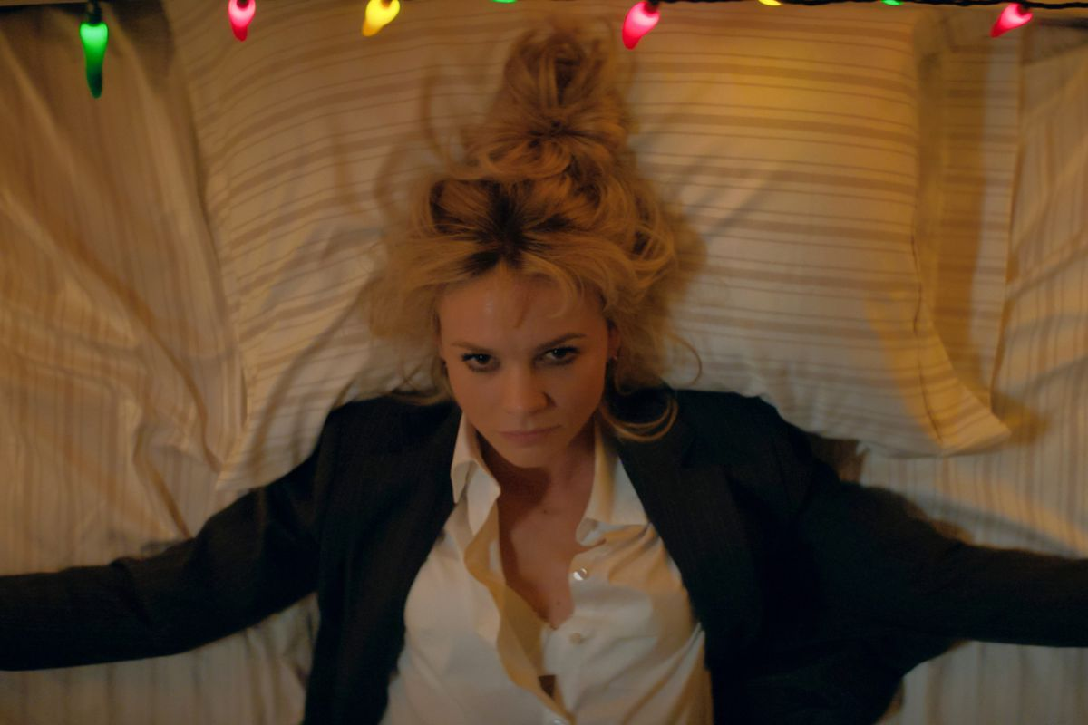 A young white woman in a white shirt and black jacket lays back against a bed, staring up blankly.