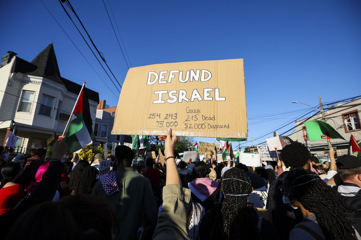 """A protester holds up a sign that reads, """"Defund Israel."""""""