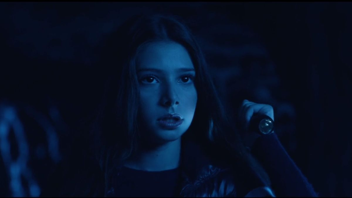 A freaked-out-looking Makenzie Moss stands in dark blue light, holding up an unlit flashlight, in Let Us In