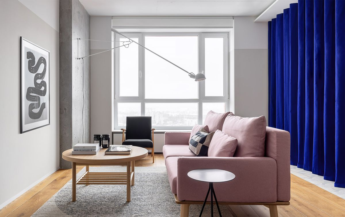 Living room with pink couch and blue curtain hanging in background.