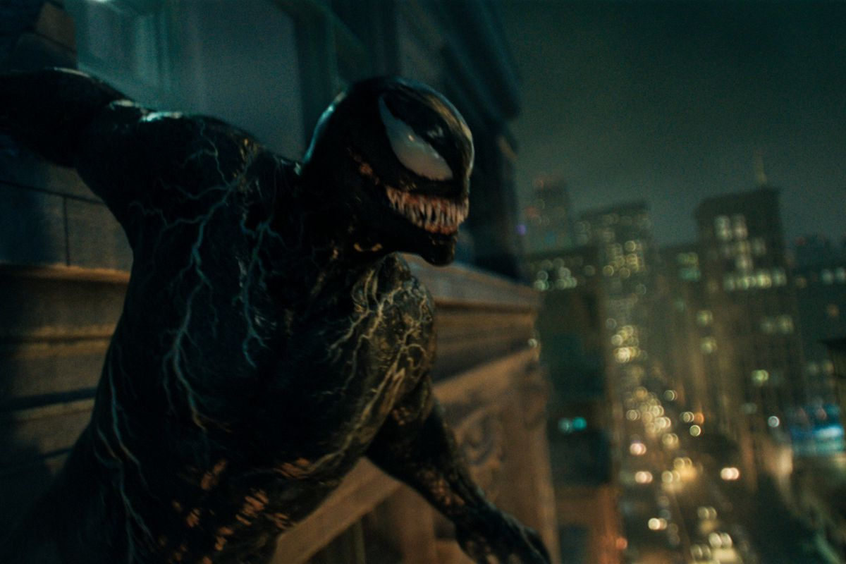 Venom perched on the side of a tall building at night with a skyline and lights below him.