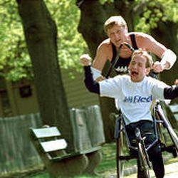 "Rick Hoyt helps his wheelchair-user son Rick ""run"" the Boston Marathon in ""America's Heart \\\\& Soul."""