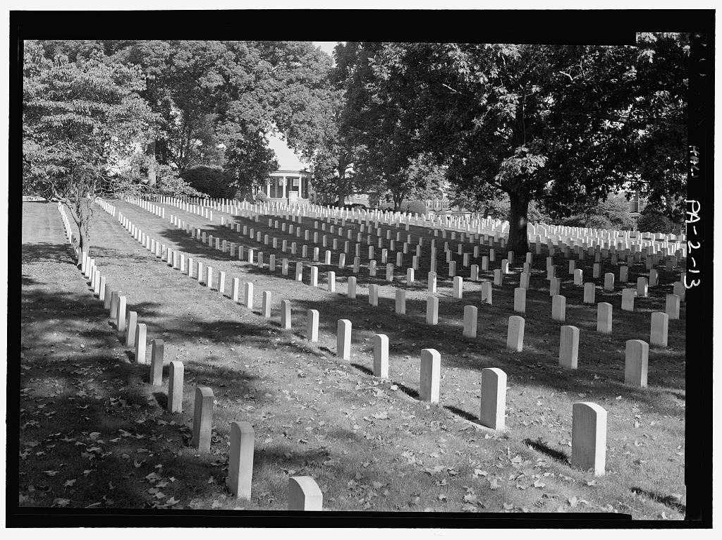 Tombstones in Philadelphia National Cemetery surrounded by trees.