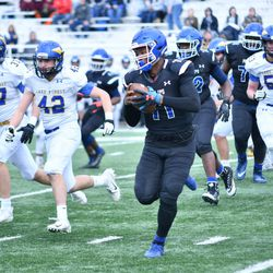 Phillips quarterback Terryon Thrower (11) gets chased out of the pocket. Worsom Robinson/For the Sun-Times.