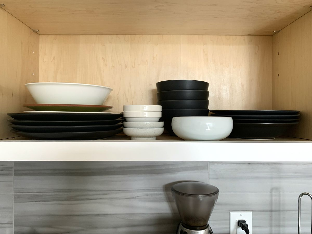 A kitchen cabinet holds stacks of plates and bowls, mostly matching pieces in black with some odd pieces in white and green.