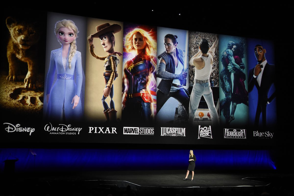 Characters from Disney and Fox movies are displayed behind Cathleen Taff, president of distribution, franchise management, business and audience insight for Walt Disney Studios during the Walt Disney Studios Motion Pictures presentation at CinemaCon 2019,