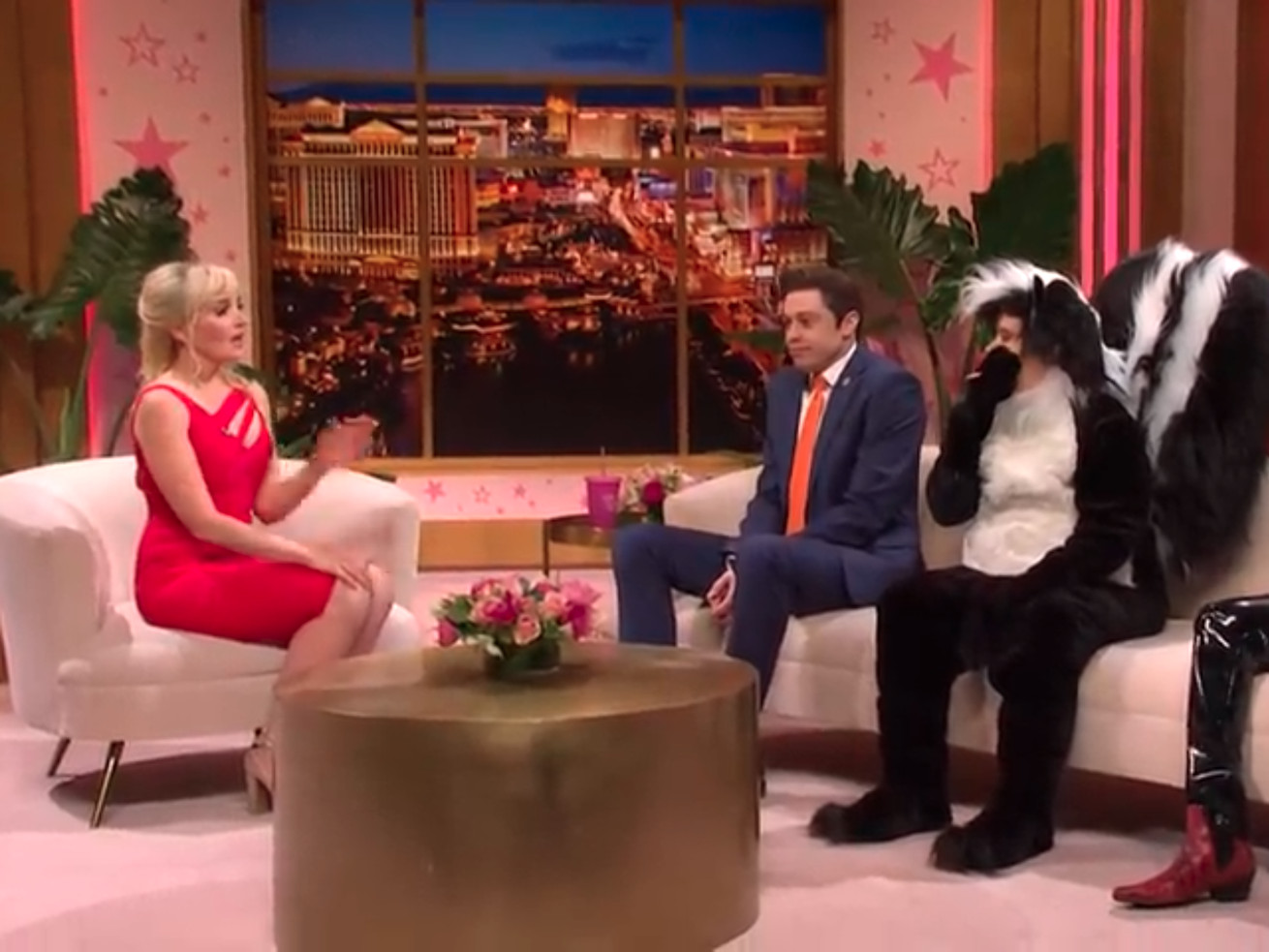 Photo shows the Saturday Night Live cold open segment Oops, You Did It Again featuring Pete Davidson as Rep. Matt Gaetz, Chloe Fineman as Britney Spears, Chris Redd as Lil Nas X, and Kate McKinnon, wearing a skunk suit, as Pepé Le Pew. They are seated on a couch and are acting in a mock talk show.