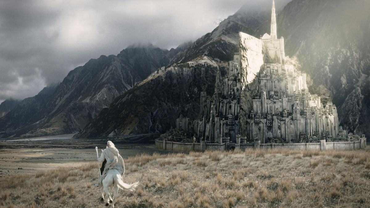 Gandalf (McKellen), clad in white and riding a white horse, approaches a city built out of the side of a mountain.