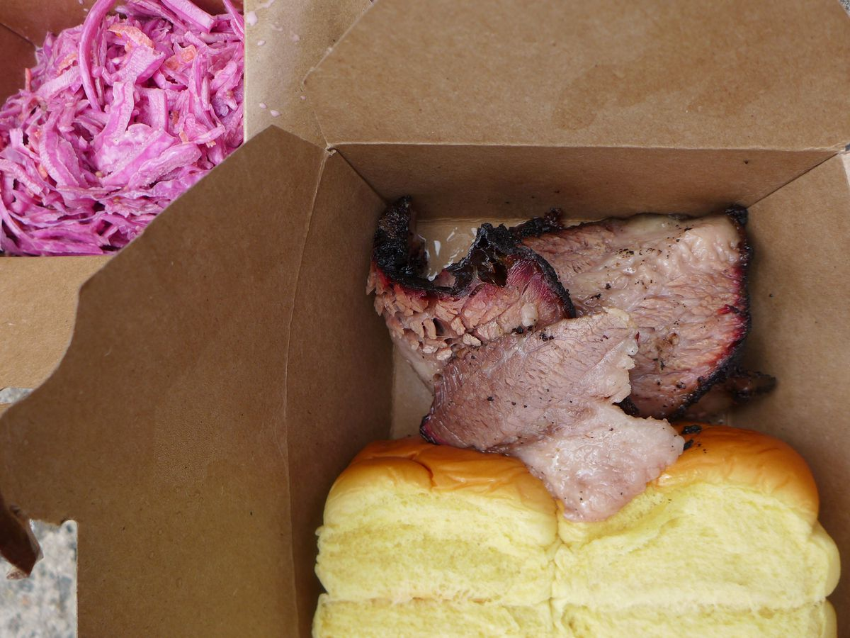 A brown cardboard box with sliced brisket and rolls seen from above, with pink cole slaw in the side.