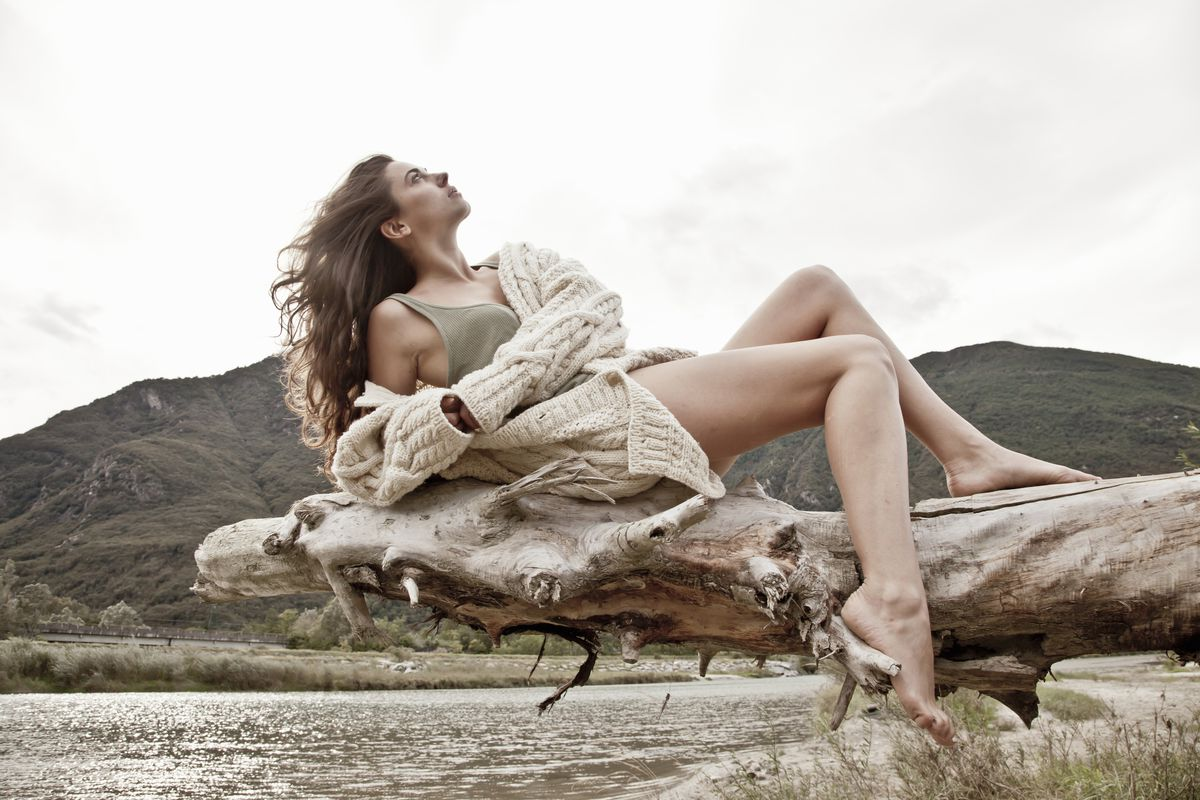 A woman in a cardigan posing on a piece of driftwood over a lake