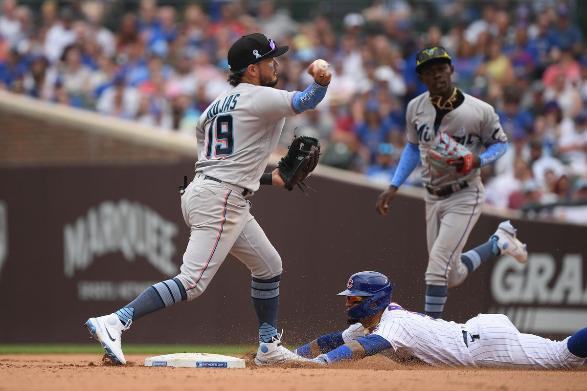 Miami Marlins shortstop Miguel Rojas (19) turns a double play in the sixth inning against Chicago Cubs shortstop Javier Baez (9) at Wrigley Field.