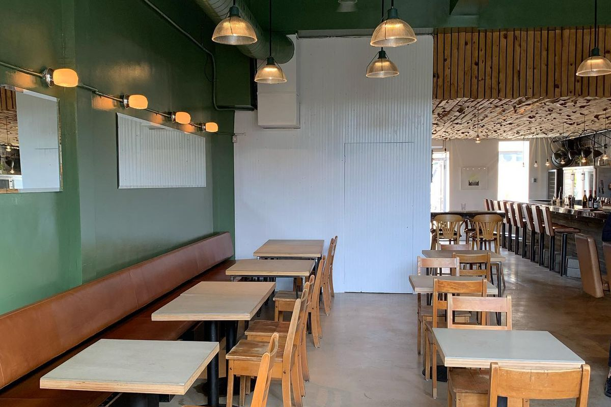 inside of restaurant with green walls and wooden chairs