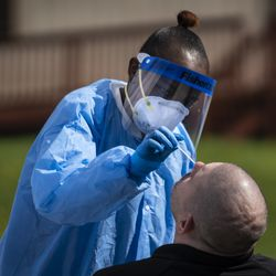 Phlebotomist Crystal Bovan, with Simple Laboratories, collects a nasopharyngeal swab sample to test for the coronavirus for a man at the lab's drive-thru testing site in the parking lot of St. Rosalie Catholic Parish in Harwood Heights, Friday, May 1, 2020.