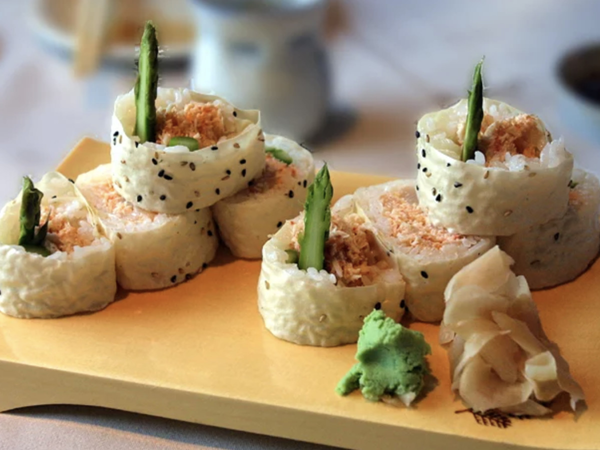 A signature sushi roll at Tangletown, with a green vegetable sprouting out from each piece.