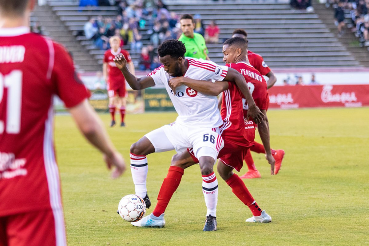 USL Photo - Toronto FC II's Malik Johnson shields the ball from a Richmond defender at City Stadium in Wednesday's 2-1 loss to the Kickers