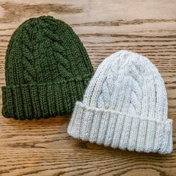 """<b>Strathtay Hand Knits</b> hats, <a href=""""http://store.inventorymagazine.com/collections/accessories/products/cable-knit-hat-natural"""">$100</a> each"""