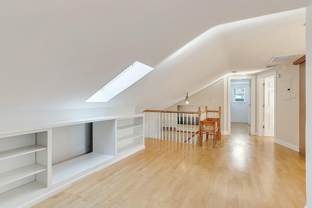 An empty room at the top of some stairs, with skylights.