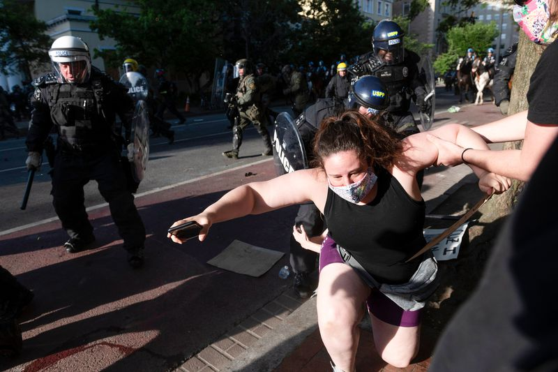 Protesters struggle to hold back armored security forces striking out at a masked woman struggling to get to her feet; a man in black pulls her up.