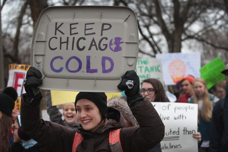 """A woman at a climate strike holds a sign that reads, """"Keep Chicago cold."""""""