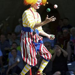 A clown on a unicycle juggles for the crowd  of spectators as they watch the floats, horses and celebrities participate in the Days of '47 Parade in Salt Lake City Saturday.
