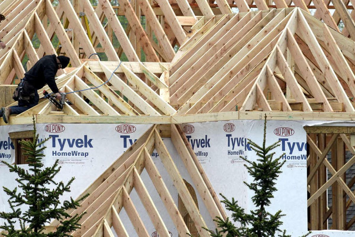 Two workers install roof joists on a new home Tuesday, May 17, 2011.