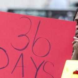 Keon McCloud holds a sign referencing the 36 days that have passed since 17-year-old Trayvon Martin was shot to death by neighborhood watch captain, Sunday, April 1, 2012, as thousands gather for a rally in downtown Miami, Sunday, April 1, 2012.