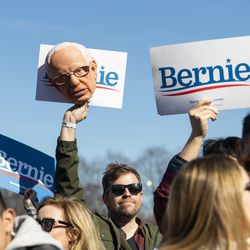 A Bernie Sanders supporter holds up a Bernie Sanders mask and sign during the candidate's rally Saturday, March 7, 2020 in Grant Park.