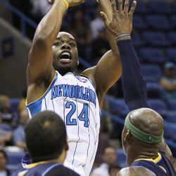 New Orleans Hornets forward Carl Landry (24) shoots over Denver Nuggets guard Andre Miller (24) and forward Al Harrington during the first half of an NBA basketball game, Wednesday, April 4, 2012, in New Orleans.