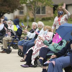 Highland Glen Assisted Living residents sit on the sidewalk as the Highland City Youth Council, city officials, police officers and firefighters participate in a drive-by parade for the residents of Highland Glen Assisted Living in Highland on Wednesday, May 13, 2020 to show love and support for them.