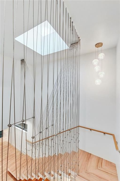 A photo of wooden, floating stairs suspended from the ceiling with thin braided steel ropes.. There's a skylight above them.