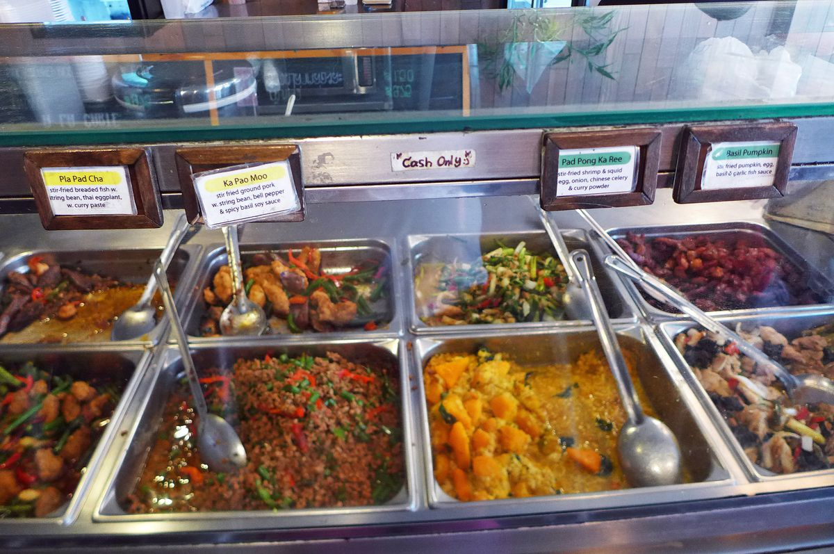 Metal trays are filled with various Thai dishes