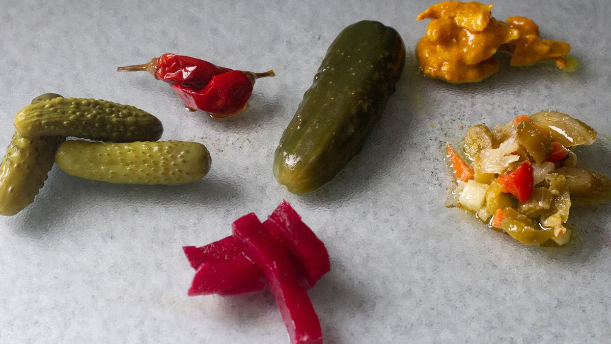 A spread of pickled vegetables laid out on a slate counter