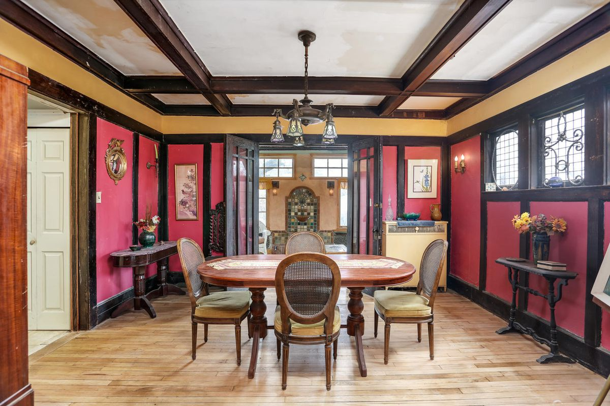 Red-painted panels are separated by dark wood molding. There's an oval wood table surrounded by four chairs.