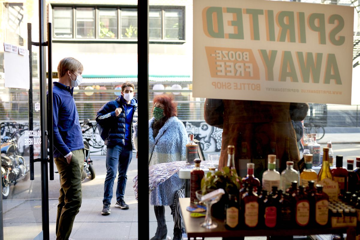 Douglas Watters, left, owner of the alcohol-free bottle shop Spirited Away, helps a customer in the Lower East Side of Manhattan in New York on Saturday, March 13, 2021. The shop is devoted to everything needed to make alcohol-free cocktails.