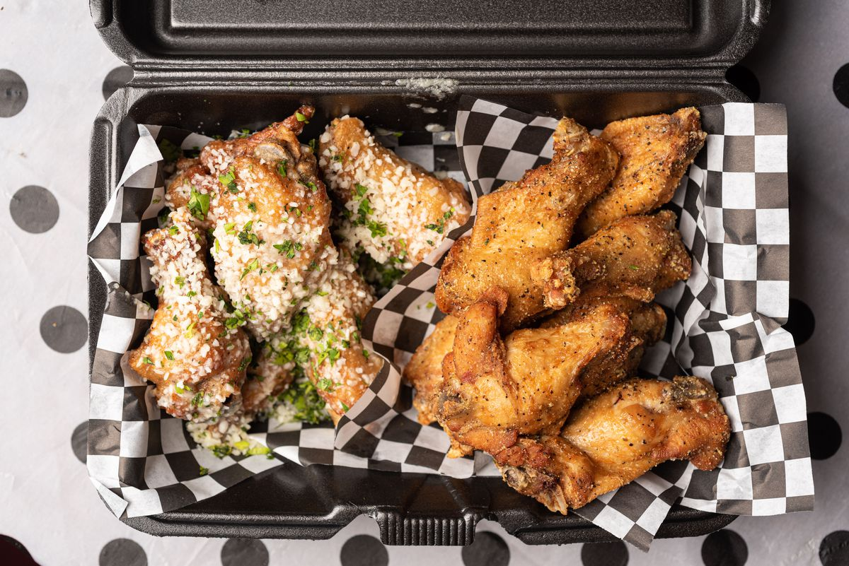 Loaded wings in black Styrofoam container, from above.