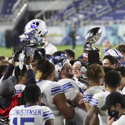 The Brigham Young Cougars players hoist the trophy after the Boca Raton Bowl in Boca Raton, Fla., on Tuesday, Dec. 22, 2020. BYU won 49-23.