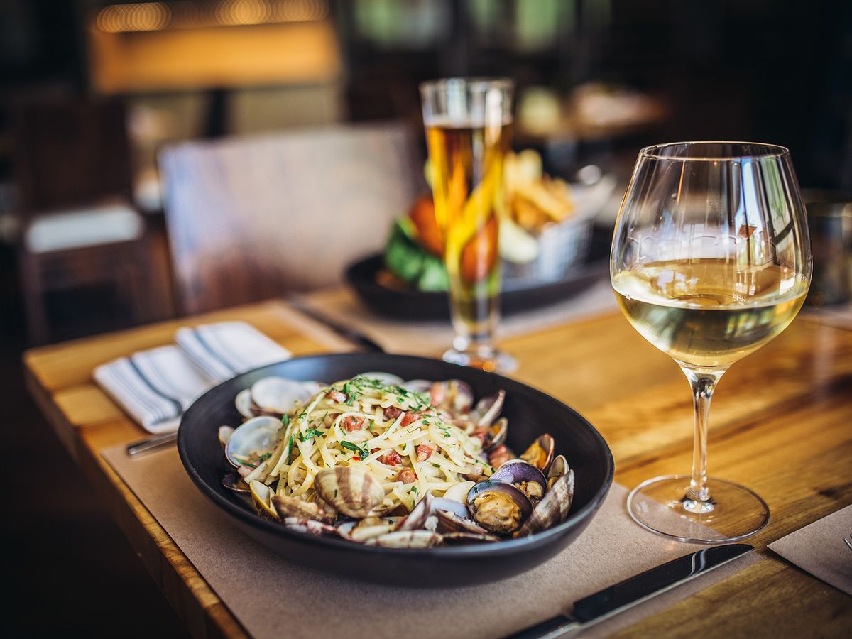 Entree on wooden table alongside glass of white wine