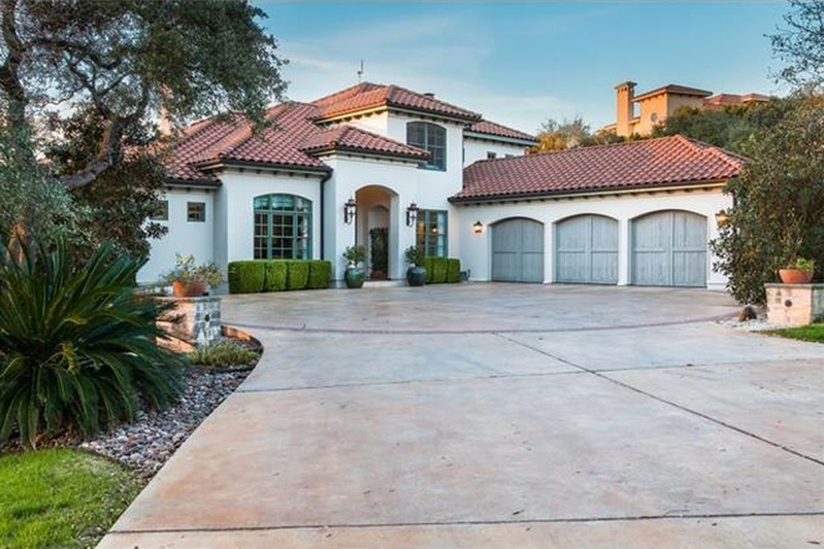 Large one-story white stucco home with ride tile roof