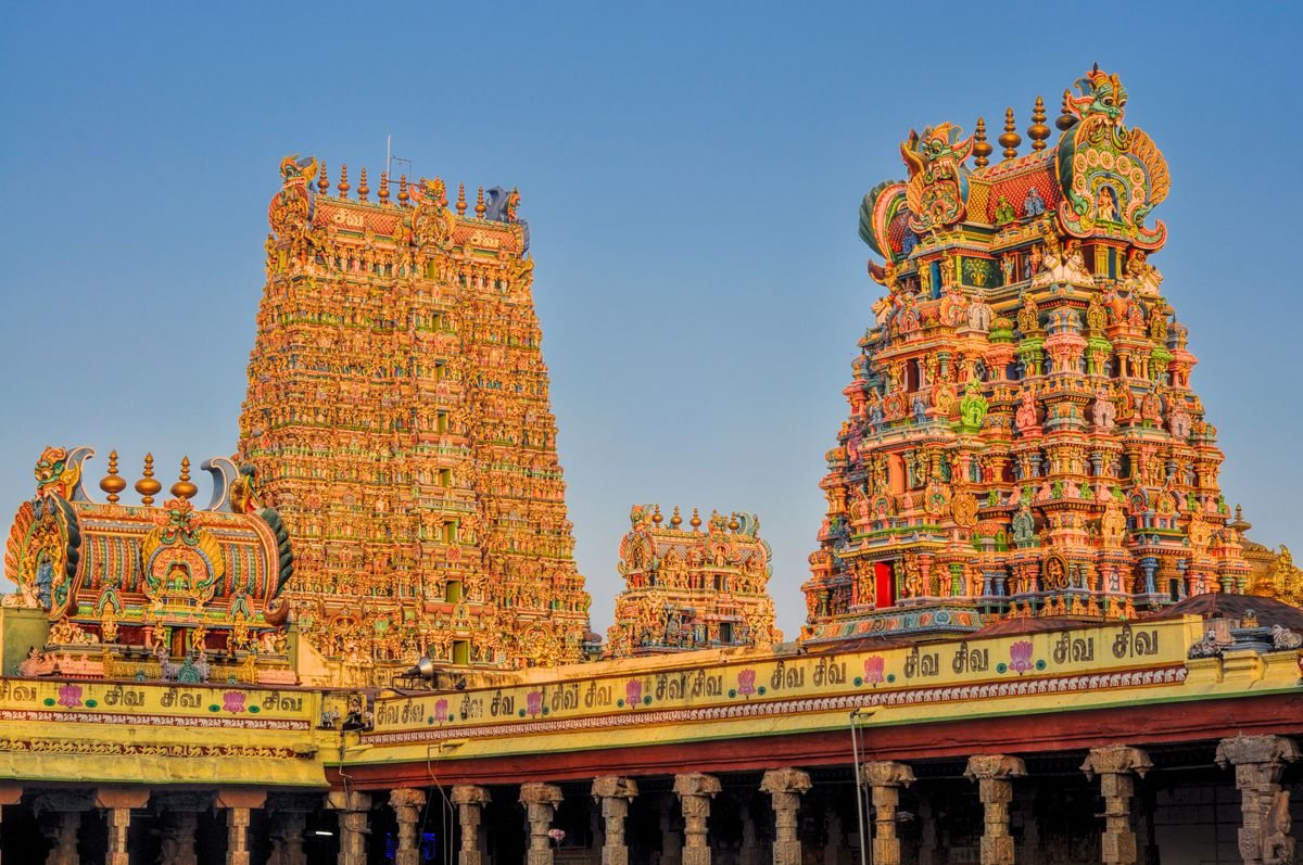 The exterior of the Meenaskshi Amman Temple in India. The facade is orange and there are colorful towers full of elaborate towers.