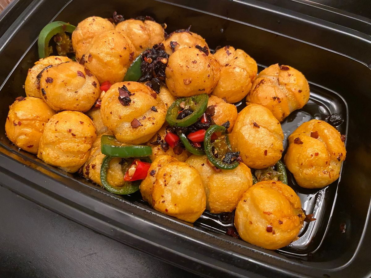 Fried glutinous rice balls topped with chiles and fermented black beans, in a takeout container