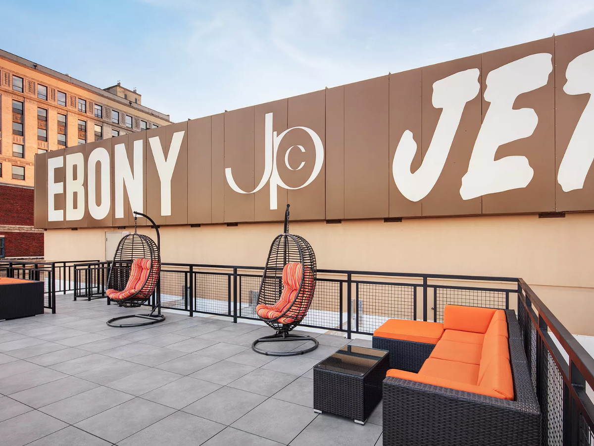 A rooftop with orange chairs and a brown sign that reads: EBONY JPC JET.